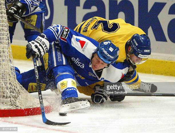 Mattias Ohlund of Team Sweden battles for the puck with Mikko Eloranta of Team Finland during an exhibition game at Globen Arena August 25, 2004 in...