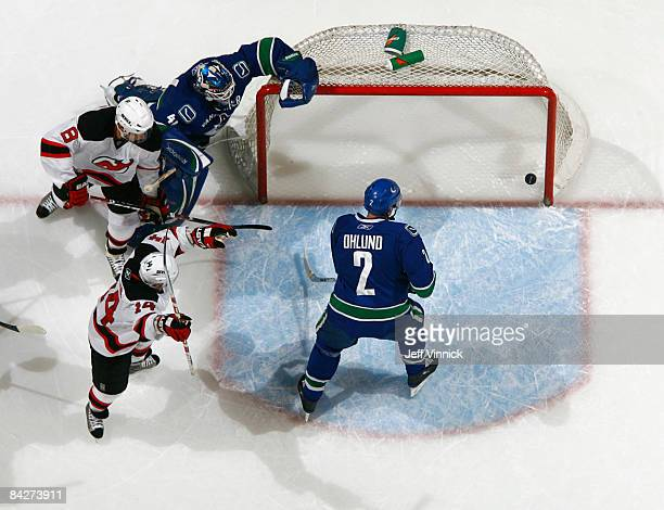 Mattias Ohlund of the Vancouver Canucks stands in the crease while goaltender Curtis Sanford crumples at the side of the net while Brian Gionta of...