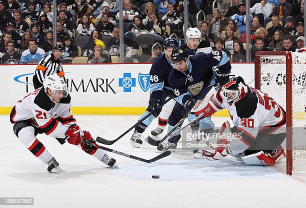 Mattias Tedenby and goaltender Martin Brodeur of the New Jersey Devils attempt to play the puck as Tyler Kennedy of the Pittsburgh Penguins skates in...