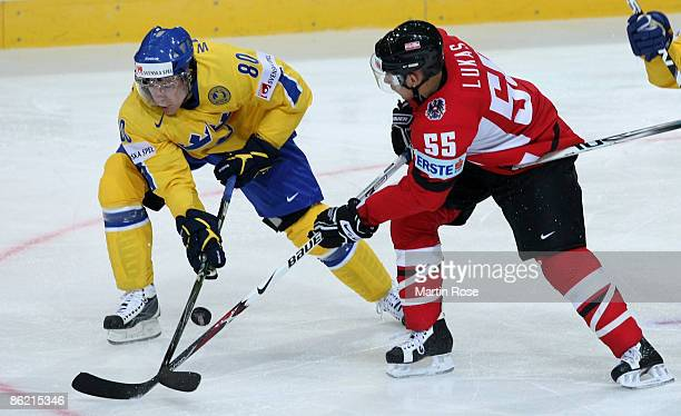 Mattias Weinhandl of Sweden fights for the puck with Robert Lukas of Austria during the IIHF World Ice Hockey Championship preliminary round, group C...