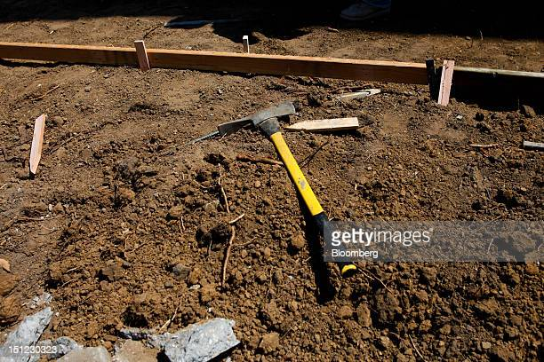 A mattock hand tool with fiberglass handle sits on a pile of dirt while workers build a concrete path for a medical building in Torrance California...