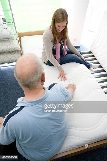 Mattresses and bed purchase Seller explained young woman the benefits of a mattress mattresses test