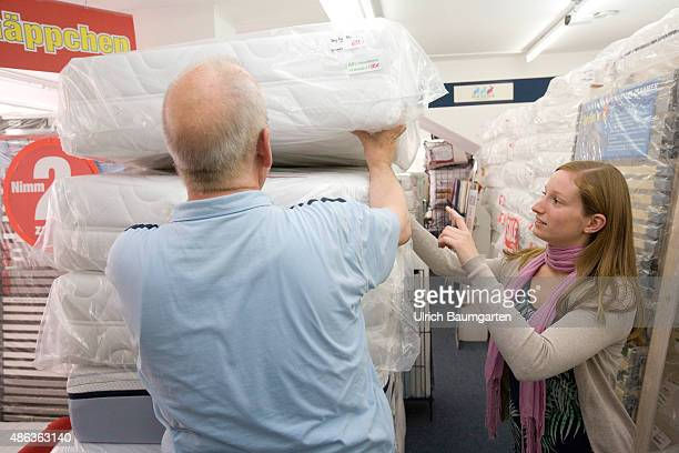Mattresses and bed purchase Seller shows young woman different mattresses