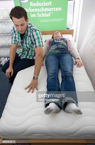 Mattresses and bed purchase Young couple sitting and lying on a mattress mattress test