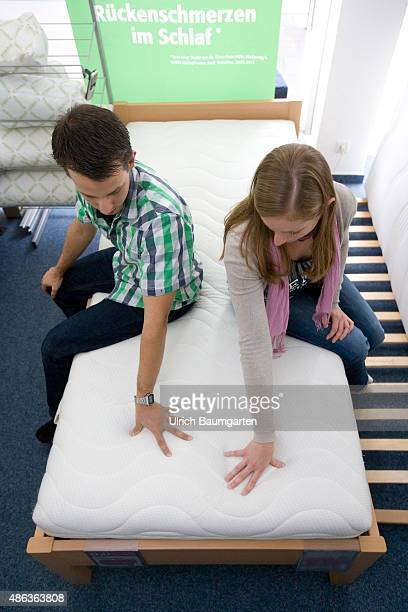 Mattresses and bed purchase Young couple sitting on a mattress mattresses test