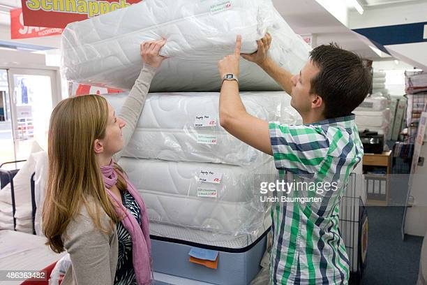 Mattresses and bed purchase Young couple stands in front of a stack of mattresses