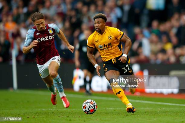 Matty Cash of Aston Villa competes with Adama Traore of Wolverhampton Wanderers during the Premier League match between Aston Villa and Wolverhampton...