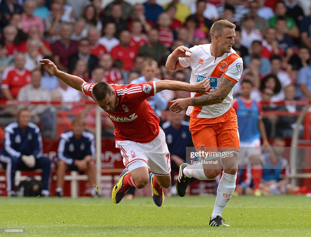 Matty Fryatt (L) of Nottingham Forest is tackled by Peter Clarke of Blackpool during the Sky Bet Championship match between Nottingham Forest and Blackpool at City Ground on August 9, 2014 in Nottingham, England.