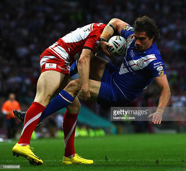 Matty Smith of St Helens is tackled by Sam Tomkins of Wigan during the engage Super League Grand Final match between St Helens and Wigan Warriors at...