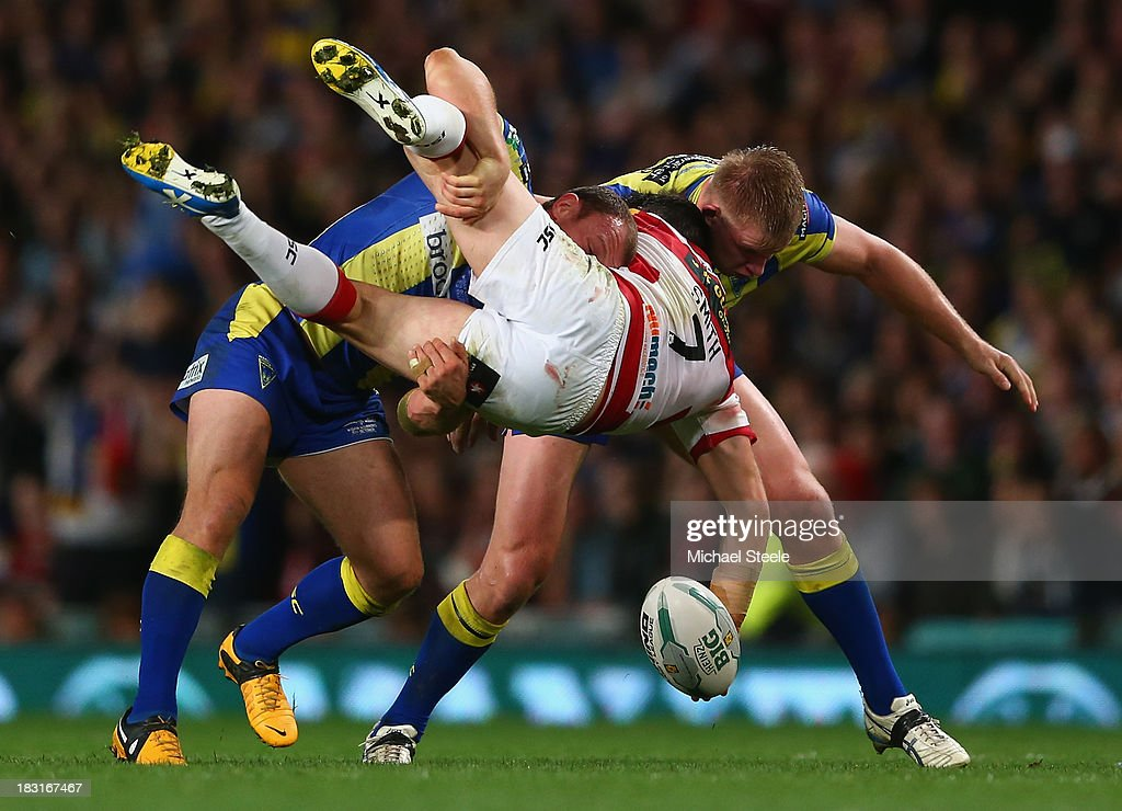 Matty Smith (C) of Wigan Warriors is upended by Micky Higham (L) and Mike Cooper (R) of Warrington Wolves during the Super League Grand Final between Warrington Wolves and Wigan Warriors at Old Trafford on October 5, 2013 in Manchester, England.