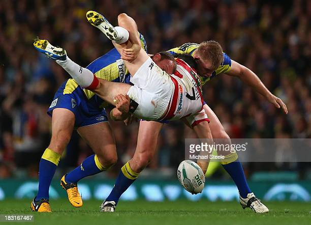 Matty Smith of Wigan Warriors is upended by Micky Higham and Mike Cooper of Warrington Wolves during the Super League Grand Final between Warrington...