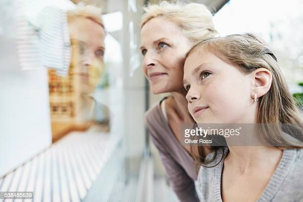 Matue woman and girl looking at shop window