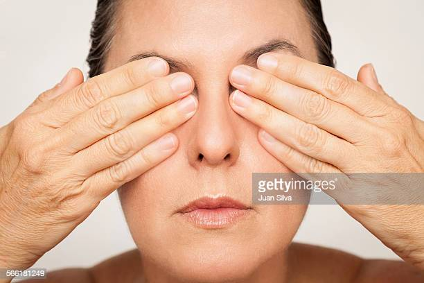 Matuire woman covering eyes with hands