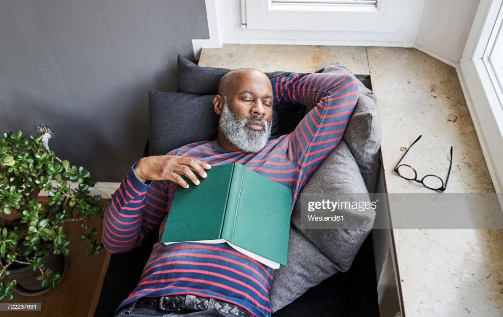 Matur man lying on bench with a book, taking a nap : Stock Photo