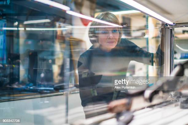 Mature 50-year-old attractive woman viewing collection of knives in the glass display