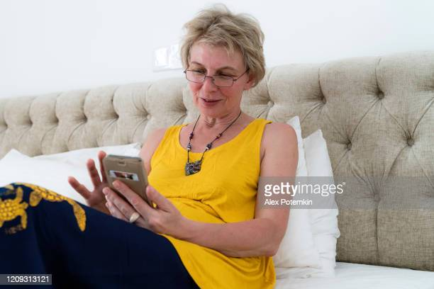 mature 55-years-old woman texting with a smartphone when she sitting on a bed in a bright and clean modern hotel room. - 55 59 years stock pictures, royalty-free photos & images