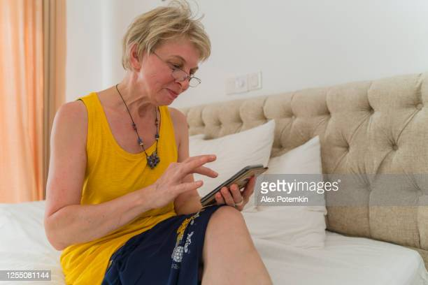 mature 55-years-old woman texting with a smartphone when she sitting on a bed in a bright modern clean hotel room. - 55 59 years stock pictures, royalty-free photos & images