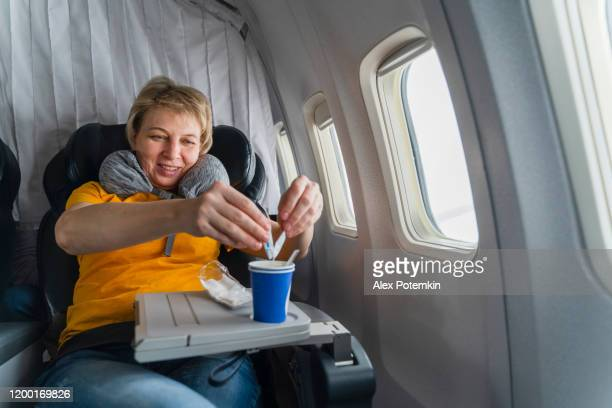 mature 55-years-old women drinking a tea in the flight, aboard of airplane. - 55 59 years stock pictures, royalty-free photos & images