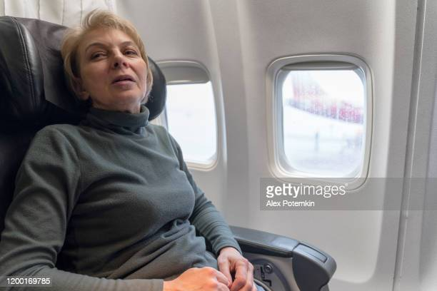 mature 55-years-old women in the flight, aboard of airplane. - 55 59 years stock pictures, royalty-free photos & images