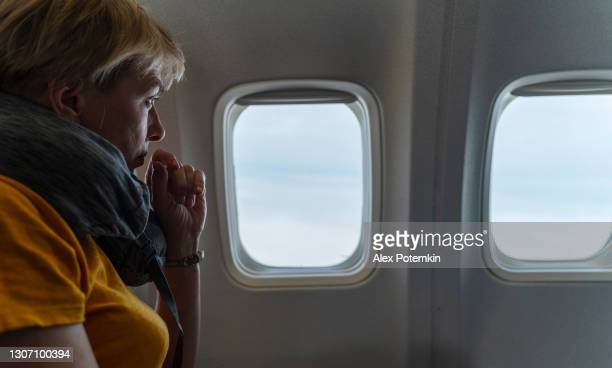 mature 55-years-old women looking into the window to the clouds in the flight, aboard of airplane. - 55 59 years stock pictures, royalty-free photos & images