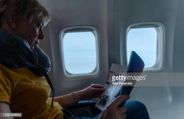 mujeres maduras de 55 años leyendo una revista en el vuelo, a bordo del avión. - 50-59 years and women only fotografías e imágenes de stock