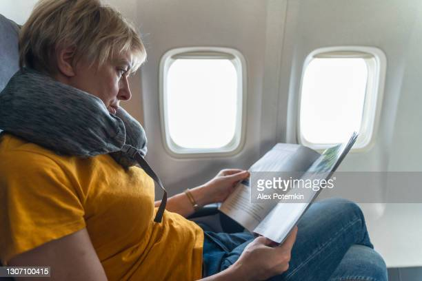 mature 55-years-old women reading a magazine in the flight, aboard of airplane. - 55 59 years stock pictures, royalty-free photos & images
