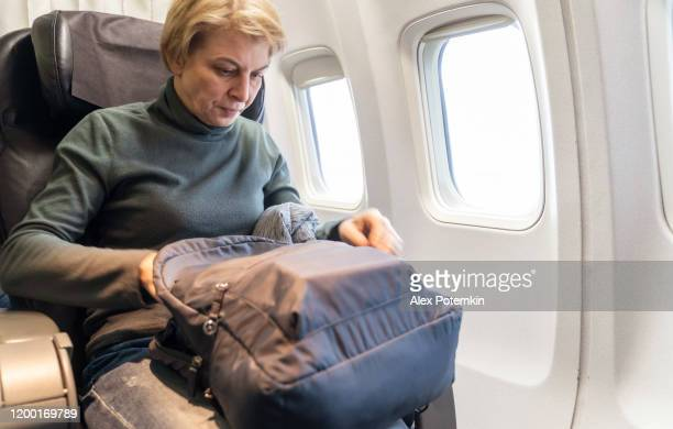 mature 55-years-old women re-packing stuff in her backpack in the flight, aboard of airplane. - 55 59 years stock pictures, royalty-free photos & images