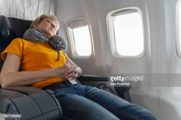 mature 55-years-old women resting during the flight, aboard of airplane. - 55 59 years stock pictures, royalty-free photos & images
