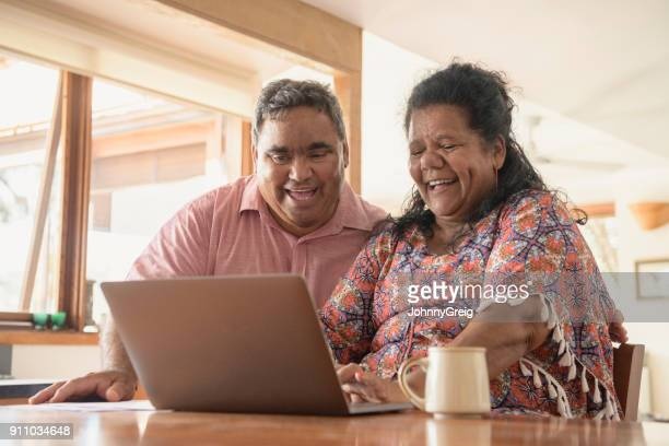 Mature Aboriginal couple looking at laptop and laughing