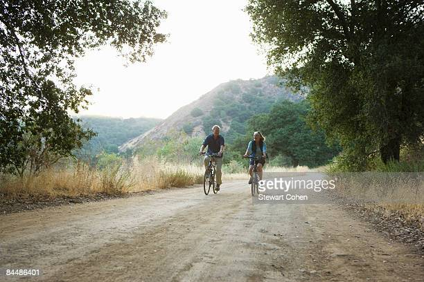 Mature active couple biking on scenic road.