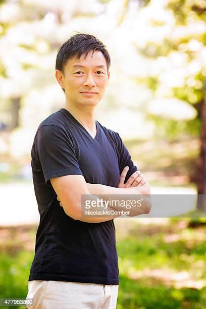 マチュアアクティブな男性のポートレート、日本の公園の t シャツの腕を組む