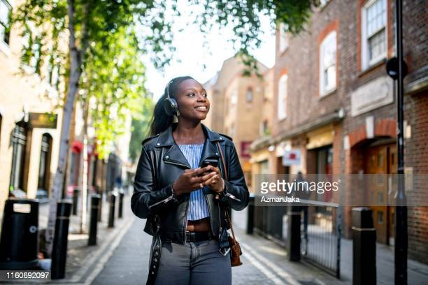 mature adult african woman listening to music while walking streets of london - walking stock pictures, royalty-free photos & images
