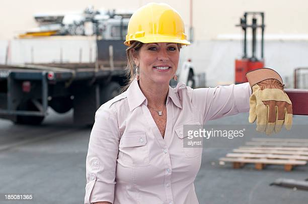 mature adult blue collar woman in a trucking yard - work glove stock photos and pictures