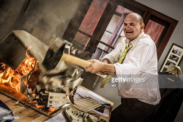 Mature adult businessman smashing computer on fire with hammer