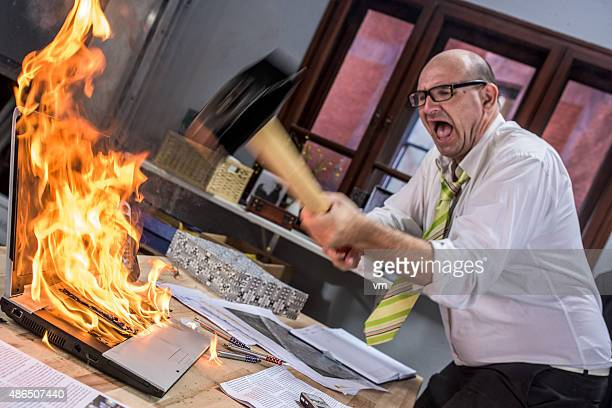 mature adult businessman smashing laptop on fire with hammer - misnoegd stockfoto's en -beelden