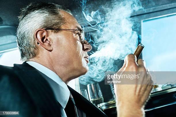 中年ビジネスマンの喫煙葉巻のリムジンます。