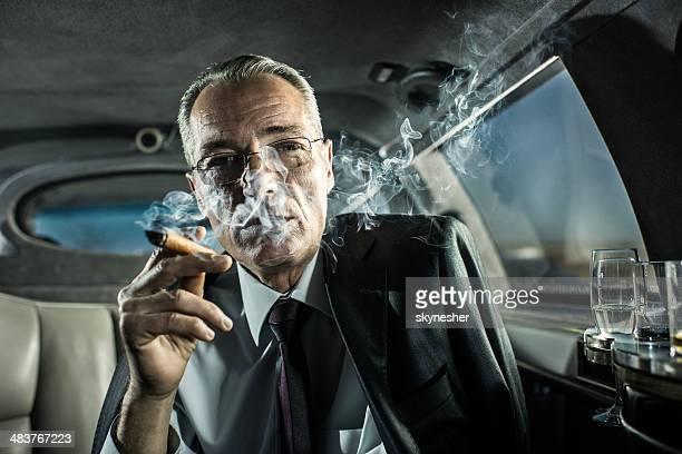 Mature adult businessman smoking a cigar in limousine.