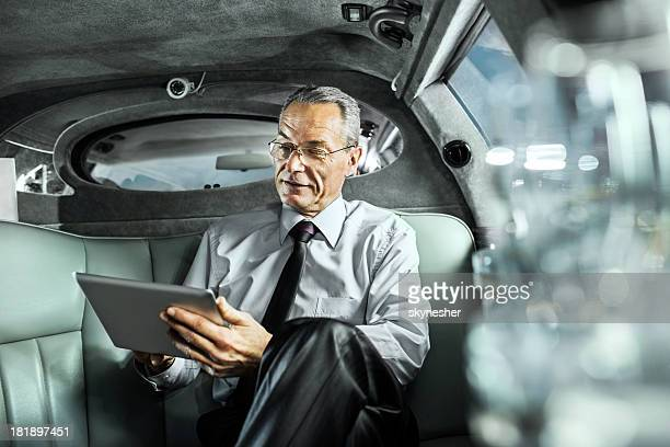 Mature adult businessman working on digital tablet in limousine.