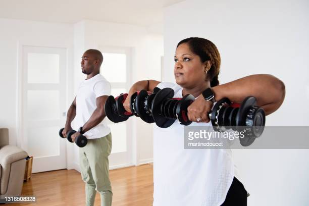 """mature adult couple doing exercise at home. - """"martine doucet"""" or martinedoucet stock pictures, royalty-free photos & images"""