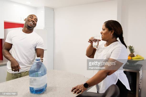"mature adult couple drinking water doing exercise at home. - ""martine doucet"" or martinedoucet stock pictures, royalty-free photos & images"