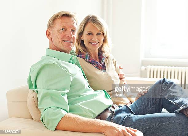 mature adult couple in their living room - husband stock pictures, royalty-free photos & images