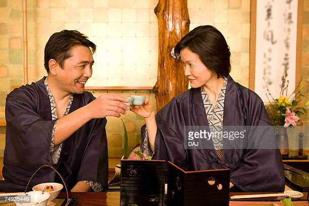 Mature Adult Couple in Yukata Toasting with Sake, Front View, Waist Up