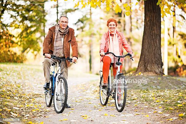 Mature adult couple riding bicycles in park.