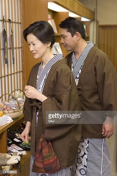mature adult couple shopping at a souvenir shop, side view, three quarter length - three quarter length ストックフォトと画像