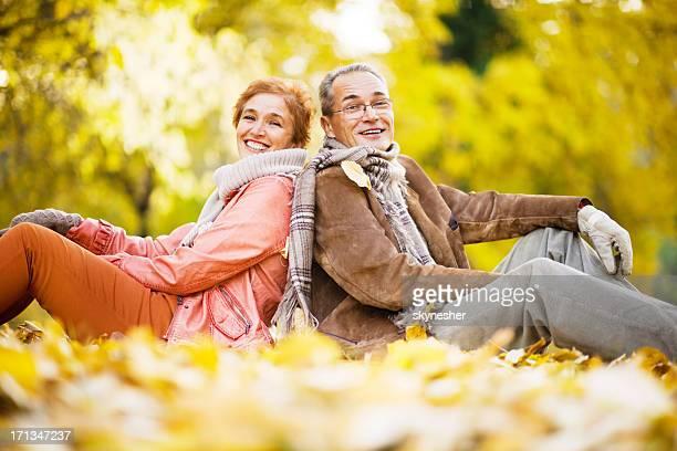 couple d'âge mûr assis dans le parc parmi les feuilles.