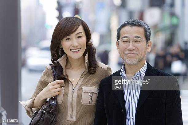 A Mature Adult Couple Smiling on a Street, Front View, Differential Focus