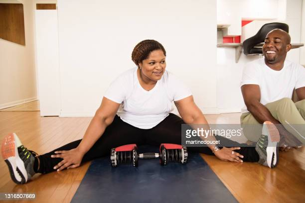 "mature adult couple taking a break while doing exercise at home. - ""martine doucet"" or martinedoucet stock pictures, royalty-free photos & images"