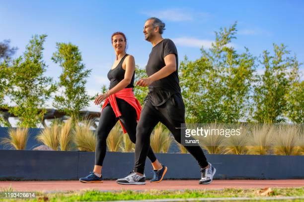 coppia adulta matura che cammina in un parco - walking foto e immagini stock