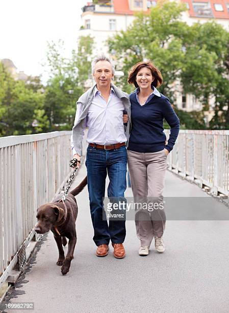 mature adult couple walking the dog - mid volwassen koppel stockfoto's en -beelden