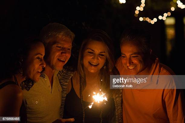 Mature adult couples playing with sparkler in garden at night